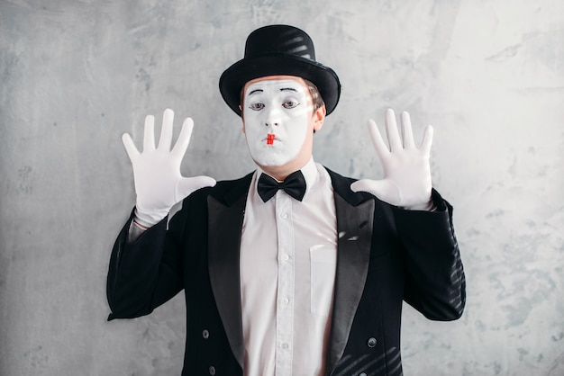Zabawny aktor mim z maską do makijażu. pantomima w garniturze, rękawiczkach i czapce.