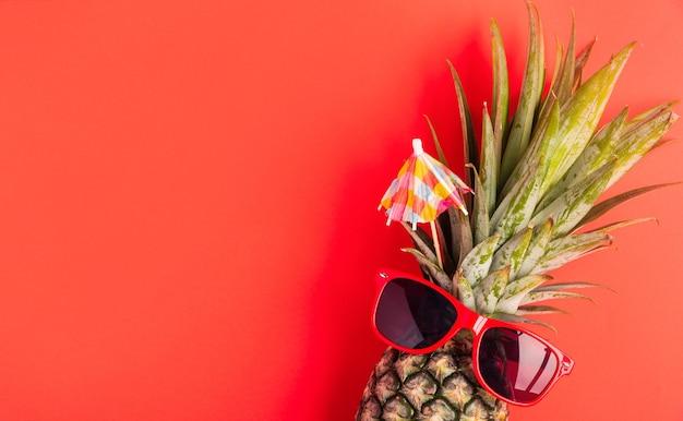 Zabawny ananas nosi czerwone okulary przeciwsłoneczne, leży płasko