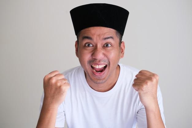 Zabawny azjatycki człowiek pokazujący podekscytowany wyraz twarzy zbliżenie