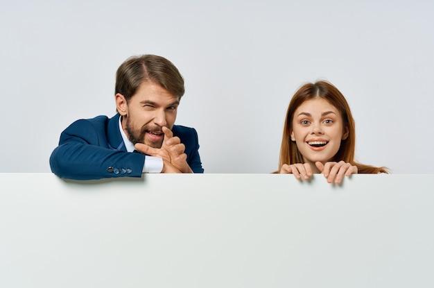Zabawny biznesmen i kobieta prezentując biały sztandar reklamowy.