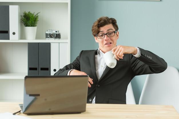 Zabawny biznesmen rozlewania herbaty w biurze