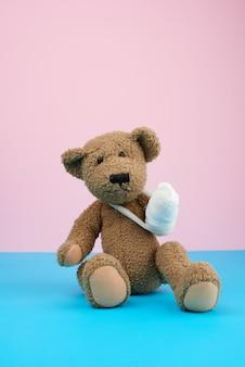 Zabawny, brązowy, kędzierzawy miś z przewiniętą łapą i białym bandażem z gazy