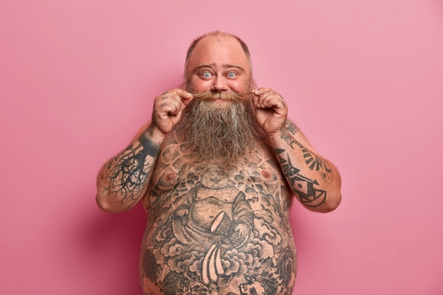 Zabawny brodacz dotyka wąsów, stoi nago z dużym brzuchem, wytatuowanym ciałem, bawi się i rozmawia z przyjaciółmi, pozuje na różowej ścianie. bez koszuli otyły facet w pomieszczeniu. ludzie, odżywianie, kształt ciała