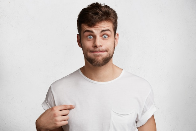 Zabawny brodaty mężczyzna naciska usta, wskazuje na pustą koszulkę