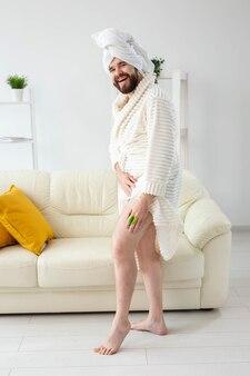 Zabawny brodaty mężczyzna nosi turbanowy ręcznik robi sobie masaż szczoteczką do masażu męskiej pielęgnacji skóry i