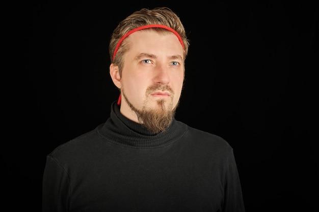 Zabawny brodaty mężczyzna z czerwoną opaską, czarne tło. młody facet w czarnym swetrze z golfem. ironiczny facet od karate