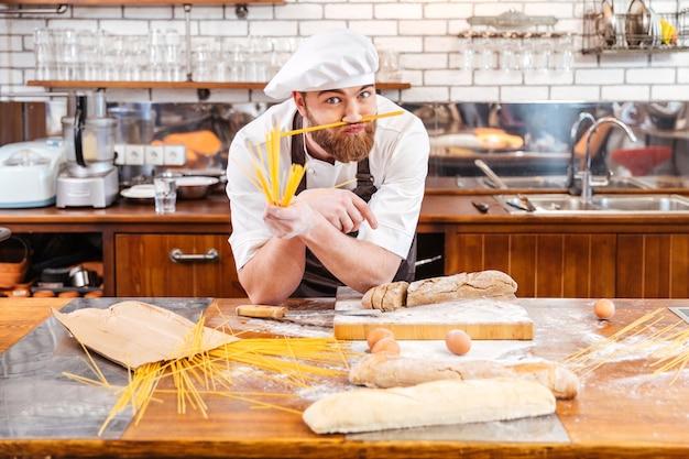 Zabawny brodaty piekarz pracujący i robiący wąsy z makaronikami i pracujący w kuchni