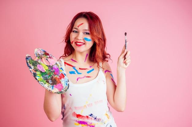 Zabawny, brudny wizażysta malarz plamy z farby na palecie twarzy w rękach na różowym tle w studio