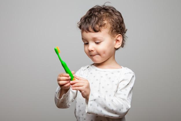 Zabawny chłopak, kręcone i słodkie dziecko z grymasem na twarzy trzyma w rękach szczoteczkę do zębów