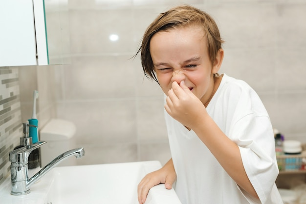 Zabawny chłopak mycia twarzy w łazience. higiena poranna. preteen chłopiec jest myty w umywalce.