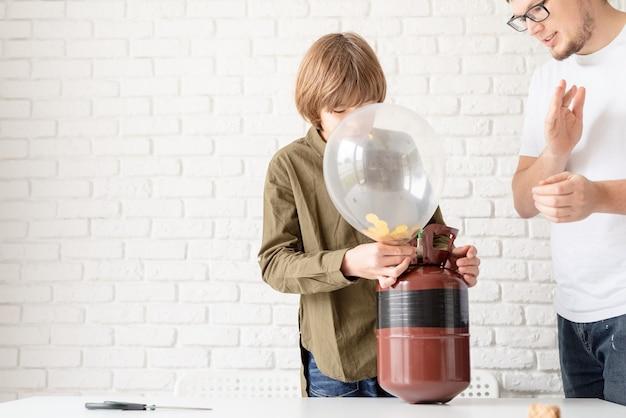 Zabawny chłopak nadmuchujący balon z helem