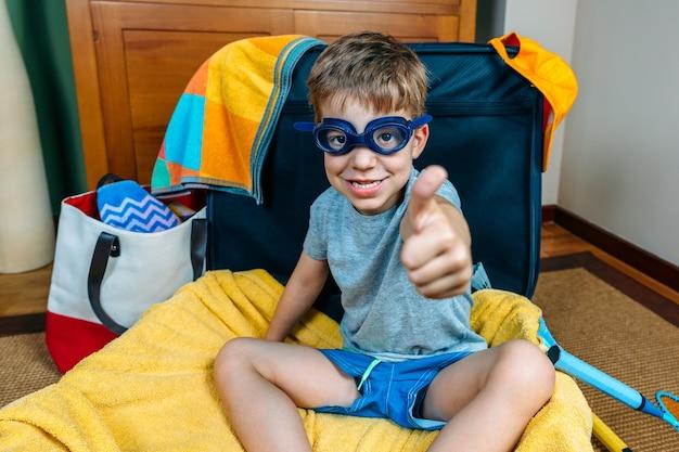 Zabawny chłopak uśmiechający się siedzący w walizce gotowy do wyjazdu na wakacje
