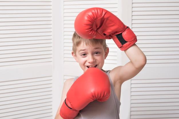 Zabawny chłopak w czerwone rękawice bokserskie. sport