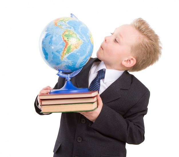 Zabawny chłopak w garniturze z globusem na książki. gotowy do szkoły