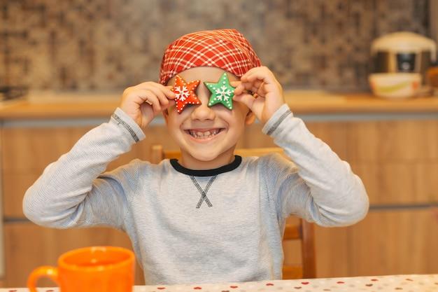 Zabawny chłopak zabawy w domu, trzyma gwiazdki ciasteczka