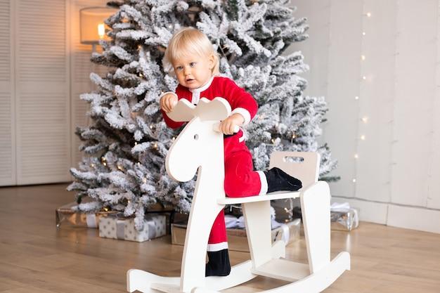 Zabawny chłopczyk siedzi na koniu-zabawce w pobliżu choinki w świątecznie urządzonym domu