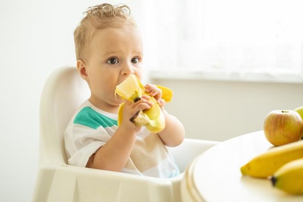 Zabawny chłopczyk siedzi przy stole w fotelu dziecko jedzenie banana w białej kuchni.