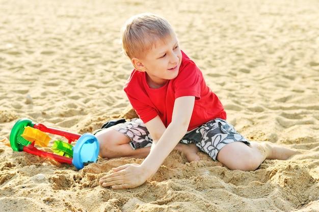 Zabawny chłopiec bawi się piaskiem na plaży