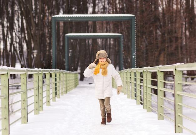 Zabawny chłopiec biegnie zimą po parku i dobrze się bawi