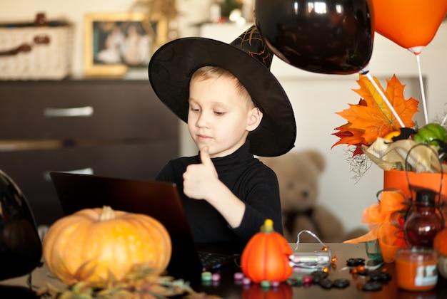 Zabawny chłopiec w stroju czarownicy na halloween za pomocą notebooka laptopa cyfrowego tabletu. zadzwoń online do znajomych lub rodziców.