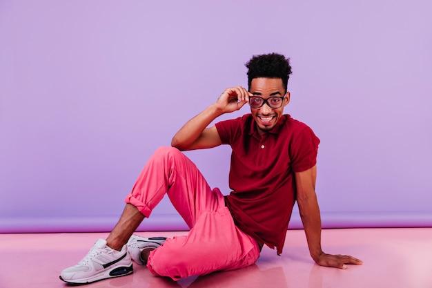 Zabawny człowiek afryki z krótkimi włosami, siedząc na podłodze. portret inspirującego faceta w okularach, żartobliwie pozowanie.