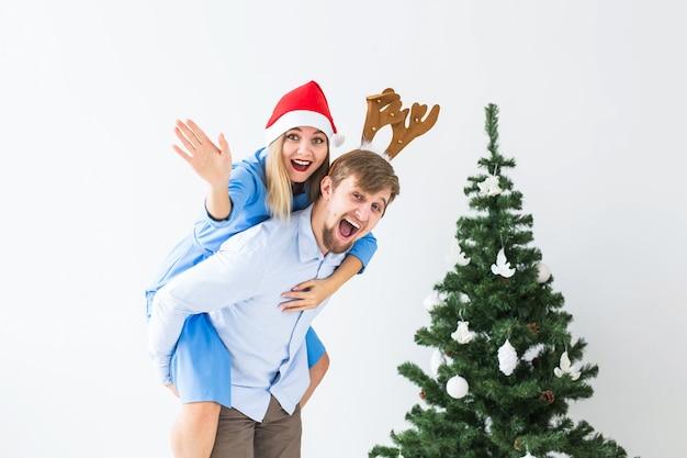 Zabawny człowiek daje na barana żonie, podczas gdy oni noszą czapki mikołaja na boże narodzenie w domu.