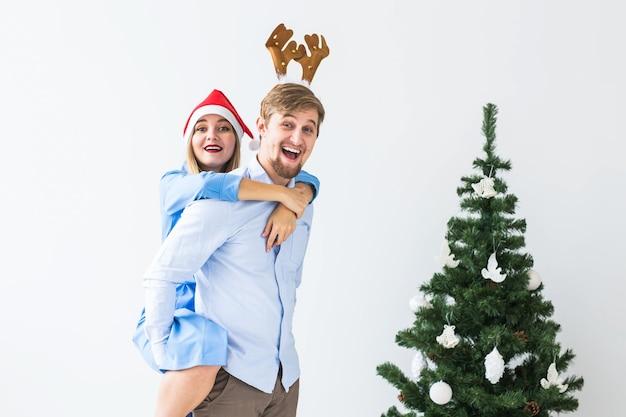 Zabawny człowiek daje piggyback żonie, podczas gdy oni noszą czapki mikołaja na święta bożego narodzenia w domu.