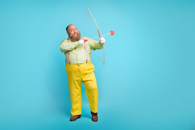 Zabawny człowiek funky strzelanie strzałkami w przestrzeń kopii na niebieskim tle