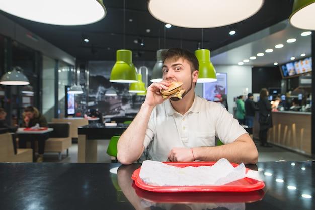 Zabawny człowiek je apetycznego burgera w restauracji. obiad fast food.
