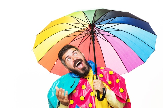 Zabawny człowiek jesieni w płaszczu pod parasolem próbuje sprawdzić, czy jest deszcz.
