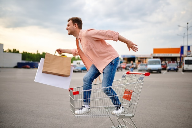 Zabawny człowiek jeździ w koszyku na parkingu w supermarkecie. zadowolony klient niosący zakupy z centrum handlowego, pojazdy, mężczyzna kupujący z paczkami