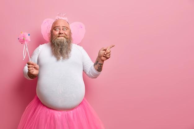 Zabawny człowiek nosi kostium wróżki, zaprasza na wakacje lub bal przebierańców, wskazuje na puste miejsce, trzyma magiczną różdżkę