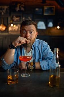 Zabawny człowiek pije koktajl alkoholowy przy kasie w barze?