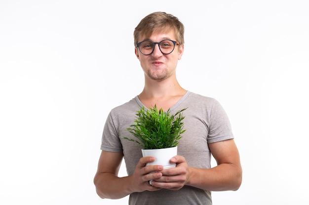 Zabawny człowiek trzyma kwiat w doniczce na białym