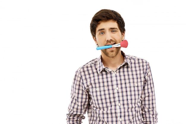 Zabawny człowiek trzyma pędzel do makijażu w ustach