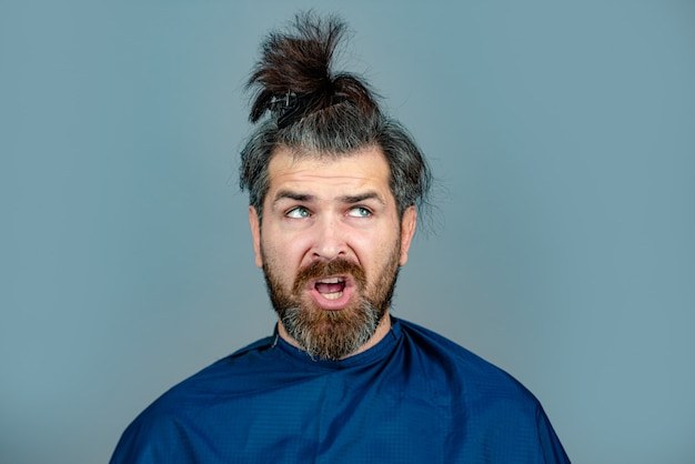 Zabawny człowiek u fryzjera coraz fryzura. hipster klient w salonie fryzjerskim. profesjonalny fryzjer fryzjerski do stylizacji włosów swojego klienta.