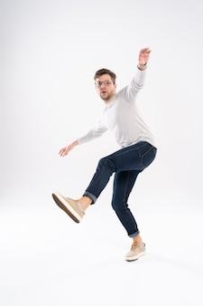 Zabawny człowiek w dorywczo t-shirt i dżinsy, skoki na białym tle nad białym tle