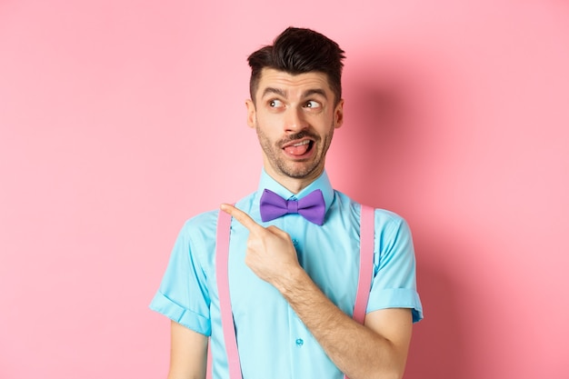 Zabawny człowiek wyraża rozczarowanie, wskazując na coś złego i pokazując język, patrząc w lewo na reklamę, stojąc na różowym tle.
