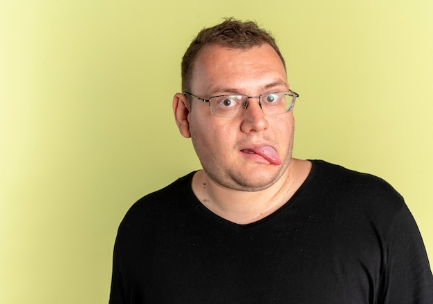 Zabawny człowiek z nadwagą w okularach na sobie czarną koszulkę wystający język na świetle