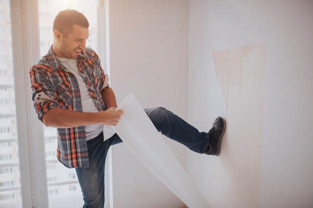 Zabawny człowiek zmienia tapetę domu. pracownik lub budowniczy trzyma w rękach filiżankę kawy i patrzy na tablet. na tle budowy i naprawy