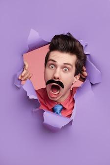 Zabawny detektyw zaglądający przez dziurę w papierze