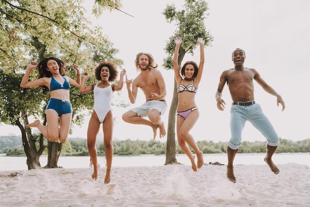 Zabawny diverse friends jump on seaside