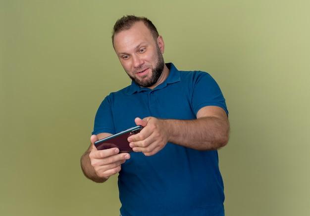 Zabawny dorosły człowiek słowiański gra na telefonie komórkowym