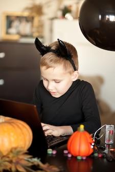 Zabawny dzieciak chłopiec w złym stroju na halloween za pomocą notebooka cyfrowego tabletu. zadzwoń online do znajomych lub rodziców.