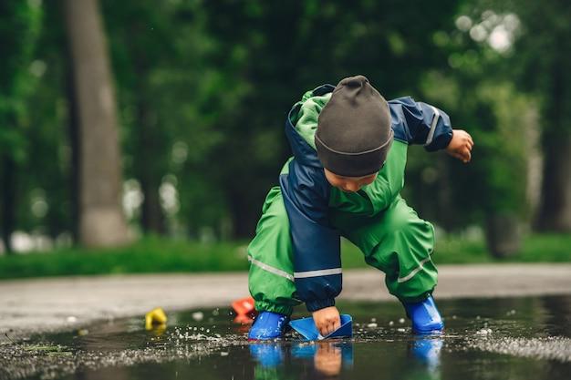 Zabawny dzieciak w kaloszach, grając w deszczu parku