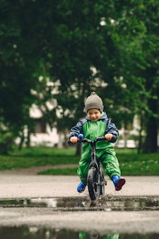 Zabawny dzieciak w kaloszach, grając w parku