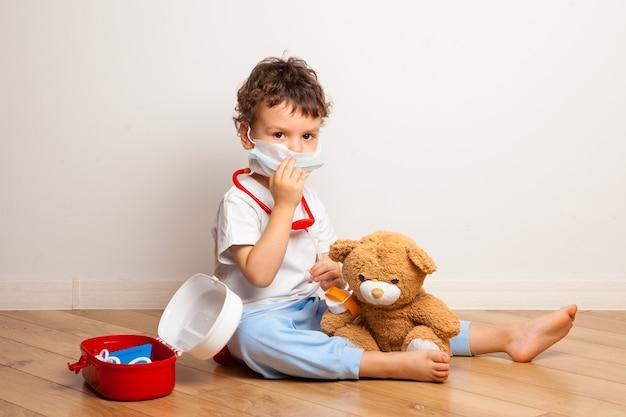 Zabawny dzieciak w masce medycznej bawi się misiem u lekarza.