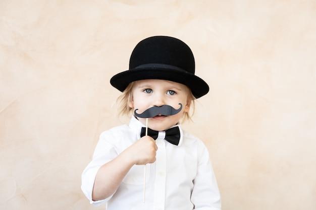 Zabawny dzieciak z fałszywymi papierowymi wąsami. szczęśliwe dziecko bawiące się w domu.