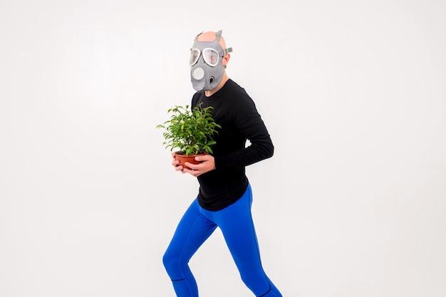 Zabawny dziwny człowiek w respiratorze z kwiatem w doniczce na białym tle