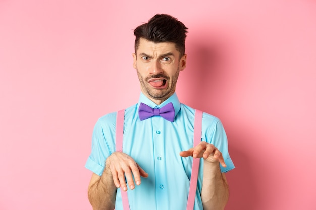 Zabawny facet patrzący na coś obrzydliwego z niechęcią i drżeniem, pokazuje język i uścisk dłoni z dezaprobatą, stojąc na różowym tle.